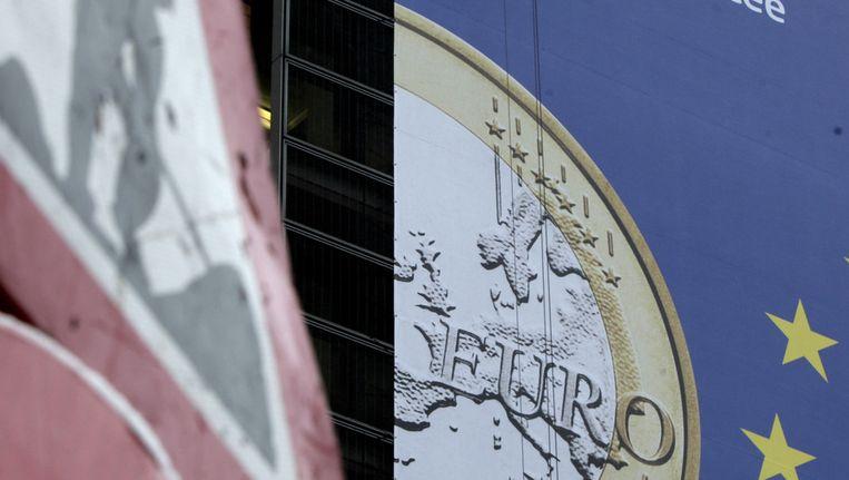 'Werk in uitvoering' tegen de achtergrond van een banier met een euromunt. Beeld ap