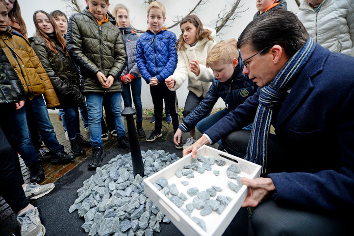 Leerlingen van de Jorisschool legden gisteren samen met burgemeester Joost van Oostrum (rechts) 101 stenen van het Holocaustmonument Levenslicht bij de synagoge in Borculo. FOTO Annina Romita