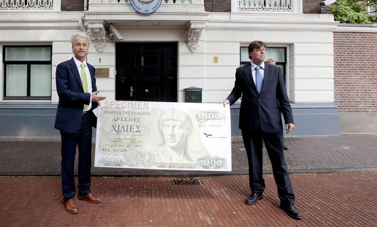 Geert Wilders (L) geeft de drachme terug aan Griekenland bij de Griekse ambassade in Den Haag. Beeld anp