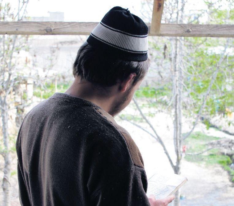 In de jeugdgevangenis van Kunduz leerde voormalig terrorist Nader Shah, die niet herkenbaar in beeld wil, lezen en schrijven. Beeld Gert Jan Rohmensen