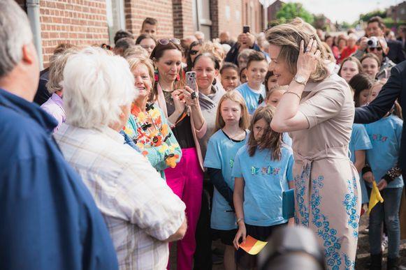 Hare Majesteit de Koningin bezoekt het gemengd landbouwbedrijf in Heers.  Verschillende mensen wachten haar op.