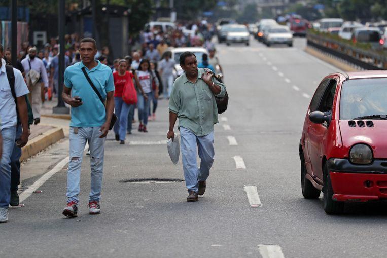 Mensen lopen over de weg in Caracas. Er is geen stroom in de hoofdstad en benzine is schaars. Beeld EPA