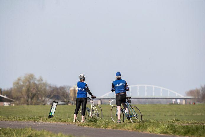 Fietsers kijken uit op de IJsselbrug bij Doesburg.