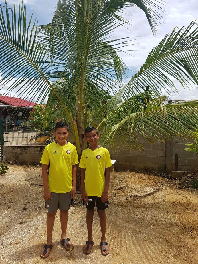 Rylan en Romano wonen in Paramaribo en zijn 'megafans' van Feyenoord, zegt Sheila Ramharakh. Het tweetal poseert trots onder de bomen in hun woonplaats.