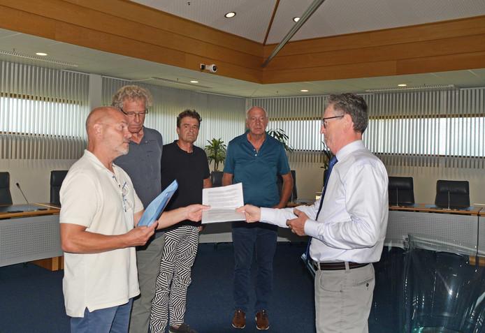 Raadsgriffier Teun van Oostenbrugge (r) neemt de brieven en petitie tegen het fietspad langs de Zeepeduinen in ontvangst van Roger Meij (l), Martin van Rossum,  Nico van Esch en Bert Coenen.