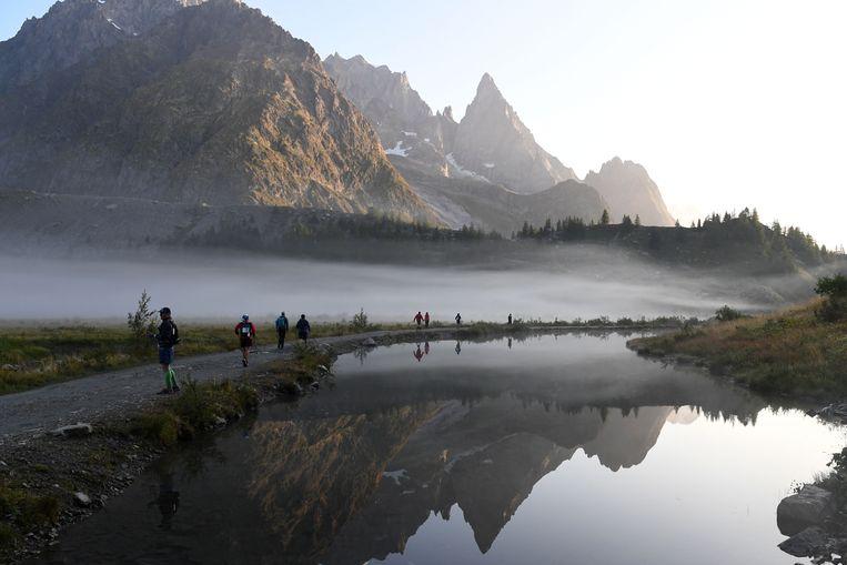 Renners passeren Lago di Combal bij  Courmayeur in Italië tijdens de 170 kilometer lange Mont Blanc Ultra Trail. Deze looptocht maakt een ronde om de Mont Blanc, door Frankrijk, Italië en Zwitserland. De snelste renners doen zo'n twintig uur over de tocht, de meesten zijn ze 32 tot 46 uur bezig. Beeld AFP