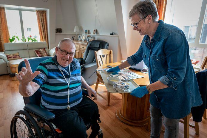 Bewoner Gerard  Spikmans van Elisabethdael in Boxtel ntvangt een maaltijd van vrijwilligster Ans van Tuijl die samen met haar man Herman maaltijden bezorgen. Zij wonen zelf ook in het complex.