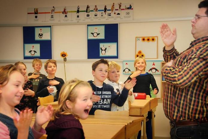Dirigent en muziekdocent Koert Dirks (rechts) laat de kinderen van groep 6 van de Mariaschool zien en horen hoe je met je blote handen muziek maakt. Foto: Mariska Hofman