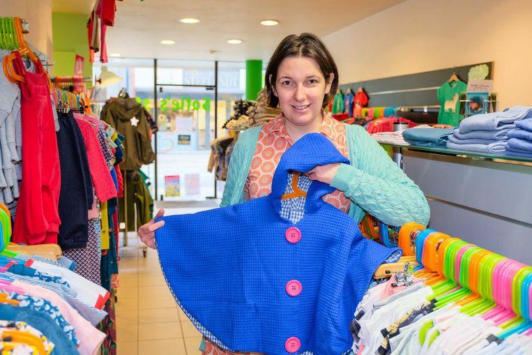 Zaakvoerster Sofie Van Goethem toont een kleurrijke cape, speciaal ontworpen voor rolstoelpatiëntjes. Het kledingstuk kan gemakkelijk al zittend aan- en uitgetrokken worden.