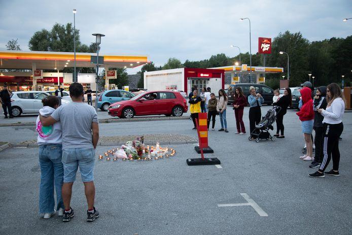 Mensen plaatsen kaarsjes en leggen bloemen bij de plaats delict:  een tankstation in Botkyrka ten zuiden van Stockholm.