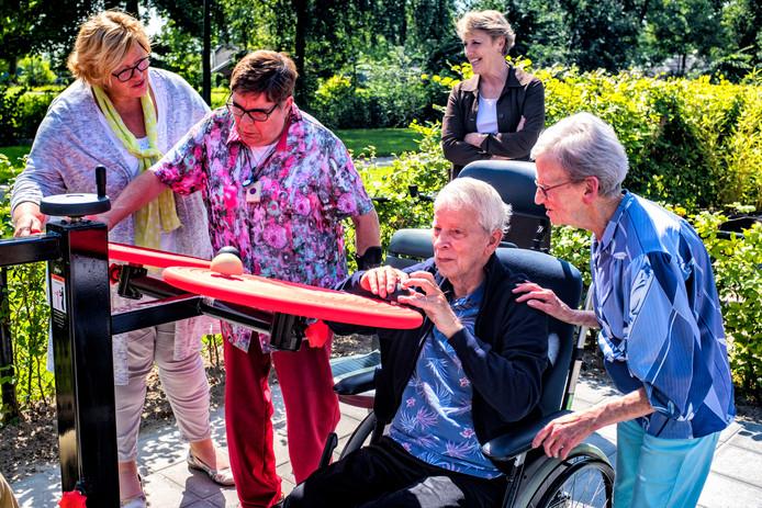 De bewoners doen enthousiast mee in de beweegtuin. Vooral Annie Sengers is bijzonder behulpzaam voor haar medebewoners. Op de foto: Ada Pauw (coördinator dagbesteding), Marriet, Trudy Prins (achter), meneer Van Stralen en Annie Sengers.