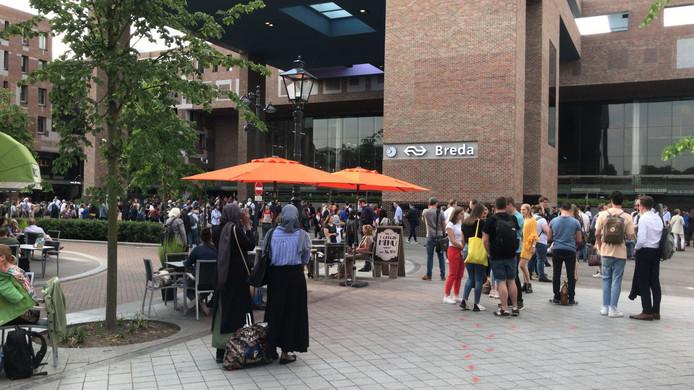 Het station is ontruimd. Mensen staan buiten te wachten op nieuws of ander vervoer.