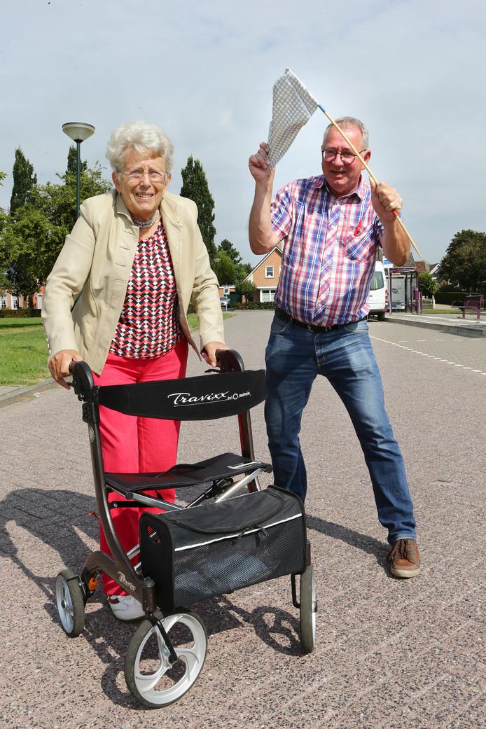 Ment Koekkoek (82) staat met haar rollator en tennisschoenen klaar voor de straatrace. Organisator Ton Damen zwaait met een geïmproviseerde startvlag.