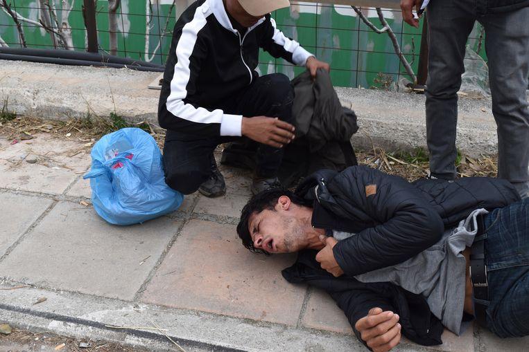 Een demonstrant komt bij, nadat de politie traangas heeft gebruikt tijdens een protest op het eiland Lesbos.  Beeld EPA