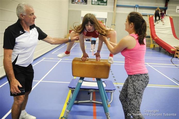 Ilke van Schooten (l) en Lara Bieshaar (r) helpen Sharon bij het aangepast sporten in De Haverkamp in Markelo.