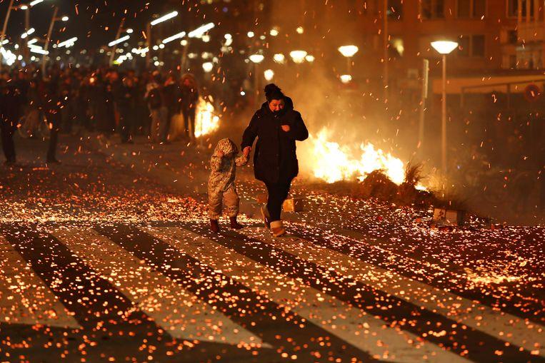 Scheveningen op nieuwjaarsdag: grote paniek op de boulevard nadat het vreugdevuur op het strand een zeer grote vonkenregen veroorzaakte die alles om zich heen in de brand stak.