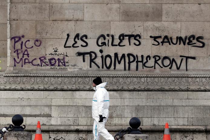 Een schoonmaker bij de met graffiti bekladde Arc de Triomphe. Er zijn leuzen op gespoten zoals 'De gele hesjes zullen overwinnen'. Het oorlogsmonument met het graf van de onbekende soldaat onder de triomfboog is gedeeltelijk vernield.