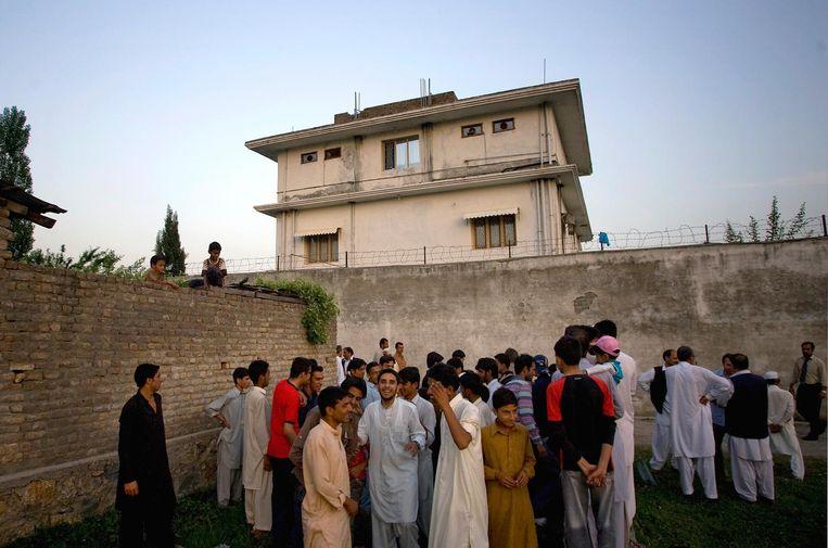 Buurtbewoners verzamelen aan het huis waar de terrorist onschadelijk werd gemaakt.