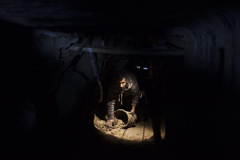 Een Palestijn is bezig met het schoonmaken van een tunnel nadat die door de Egyptische autoriteiten was volgepompt met water. Beeld epa