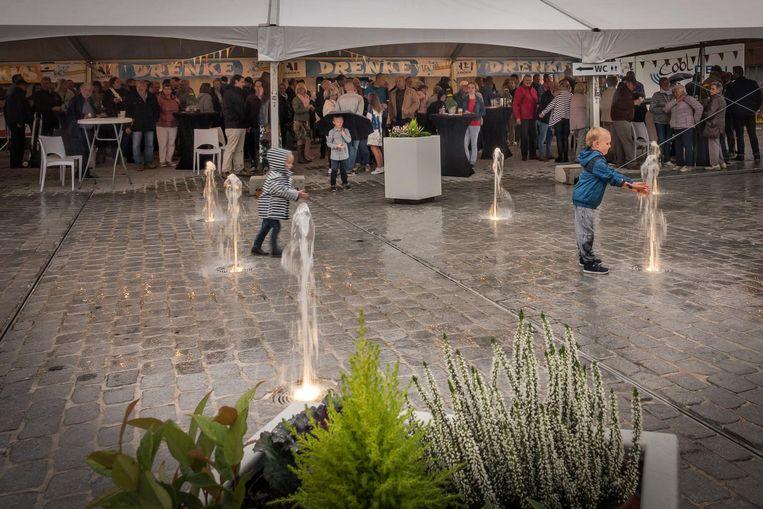 In de regen testen de kinderen de fonteinen uit.