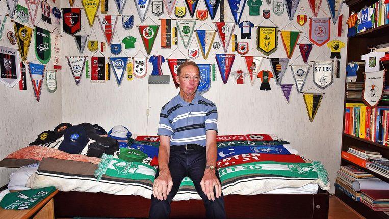John Panhuijsen (63) in zijn slaapkamer met de relikwieën van amateurclubs die hij in 32 jaar tijd heeft bezocht. Beeld Guus Dubbelman / de Volkskrant