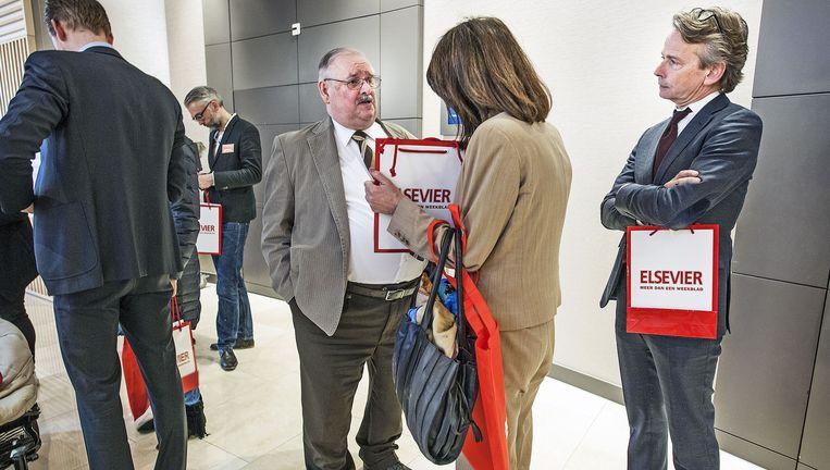 Journalisten van het tijdschrift Elsevier delen woensdag tasjes uit aan aandeelhouders. Het concern wil dat het blad zijn naam afstaat. Beeld Guus Dubbelman / de Volkskrant