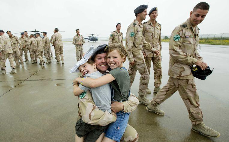Een militair wordt op vliegveld Eindhoven verwelkomd door zijn kinderen. Ruim 50 manschappen van het F-16 detachement keerden terug van hun missie in Afghanistan, 2014.  Beeld ANP