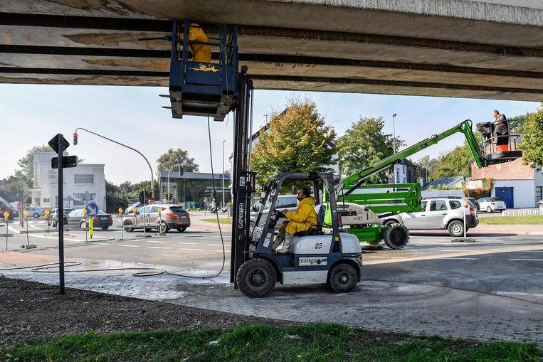 Arbeiders brengen de netten onder de spoorwegbrug aan.