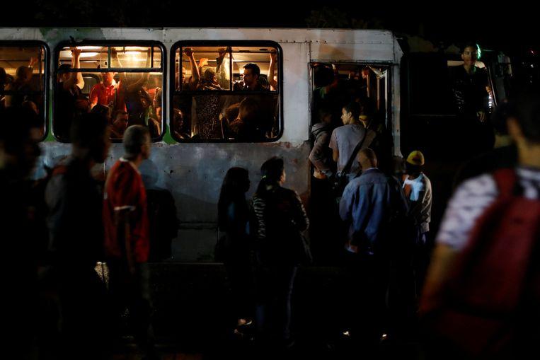 In het donker nemen mensen de bus tijdens de stroomuitval in Venezuela. Beeld REUTERS