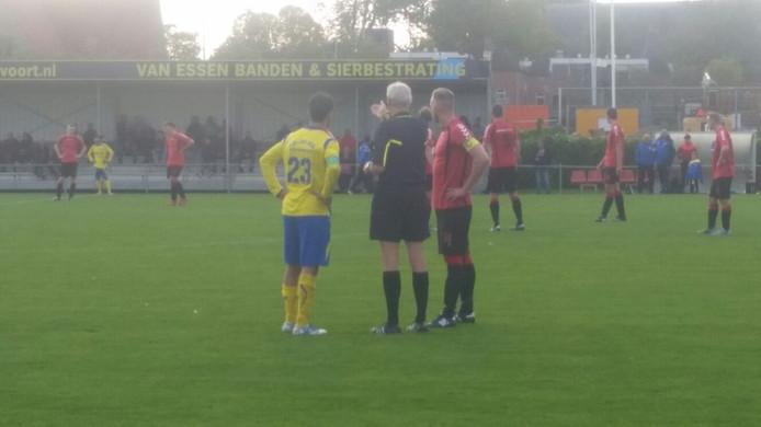 Scheidsrechter Beser spreekt de aanvoerders van AVW'66 en SC Veluwezoom toe, maar houdt de kaarten na het opstootje op zak.