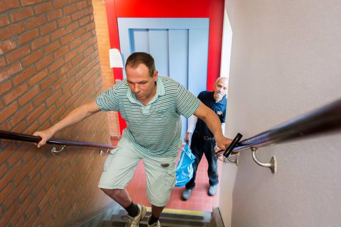 Voor Hans Bazelmans is traplopen lastig vanwege zijn spierziekte. Vrijwilliger Paul Mollet helpt hem.