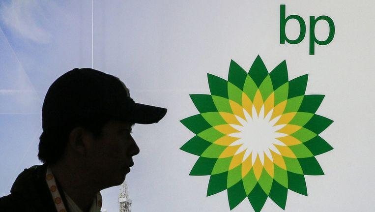 Een man loopt langs het logo van BP. Beeld epa