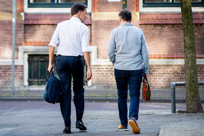 Premier Mark Rutte en fractievoorzitter Klaas Dijkhof (VVD) vertrekken bij het ministerie van Financiën na afloop van een overleg van de coalitiepartijen over de begroting voor volgend jaar.