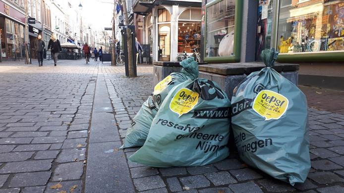 Oeps!-sticker op vuilniszakken in de Lange Hezelstraat die op verkeerde plek staan