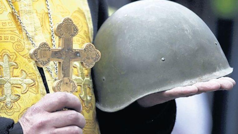 Een priester houdt een dienst voor een van de in Kiev omgekomen demonstranten. Beeld reuters