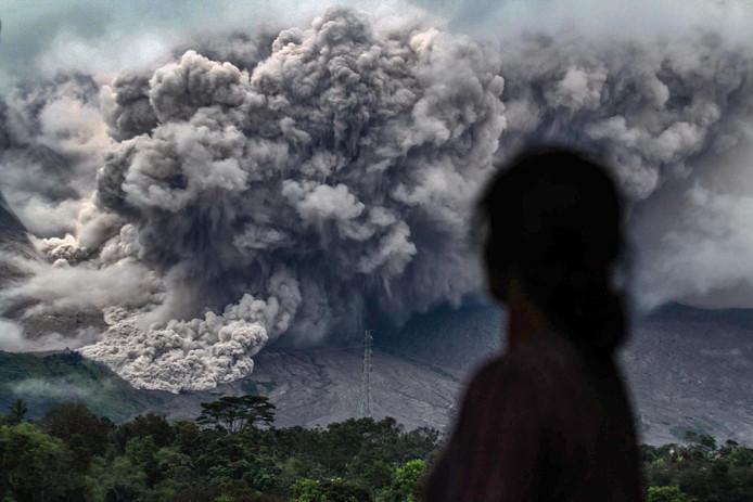 Op het Indonesische eiland Sumatra kijkt een inwoner van het dorp Tiga Pancur naar de uitbarsting  van de vulkaan Sinabung . Foto: Ivan Damanik