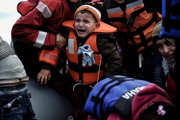 Een kind huilt als hij van de boot wordt gehaald in Lesbos. Beeld Afp