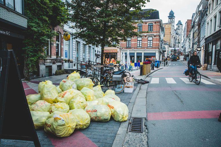 De vuilniszakken aan de terrassen.