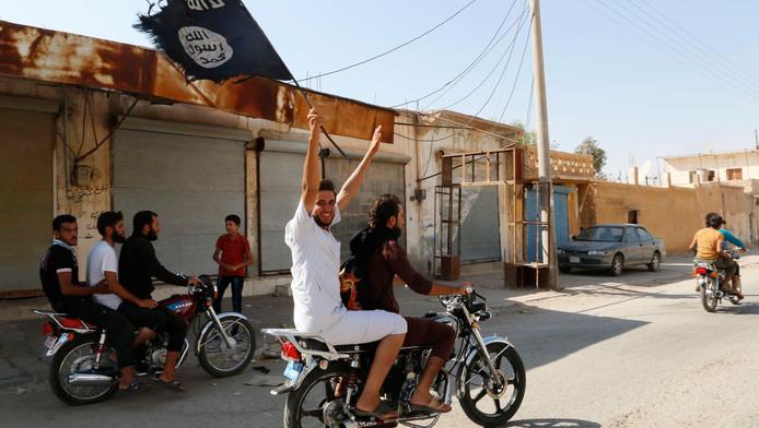 IS-aanhangers rijden met brommers door Tabqa.