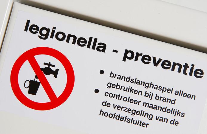 Sticker van Legionella Preventie op de gast waar de brandslang in een kantorenpand hangt.