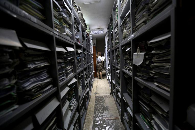 Een medewerker van het hooggerechtshof zoekt in het archief waar inmiddels meer dan 35.000 zaken wachten om in behandeling te worden genomen. Beeld AFP