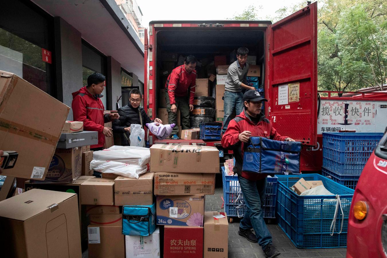 Bezorgers laden pakketten uit een truck in Peking.