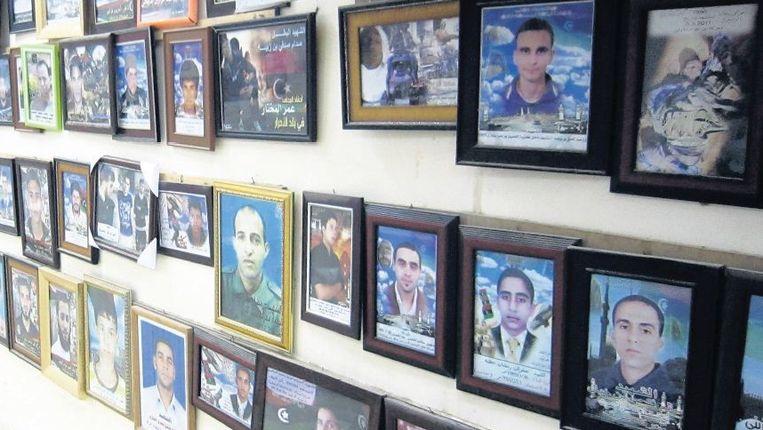 Portretten van gesneuvelde djihadisten, geflankeerd door moskeekoepels en kalasjnikovs, hangen in de Gedenkruimte van de Martelaren, op het terrein van de grote moskee in de stad Derna. Beeld Marijn Kruk