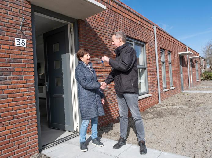Addie Lievense krijgt de sleutel van haar nieuwe huurwoning van Jacco den Boer van woningbouwvereniging Zeeuwland.