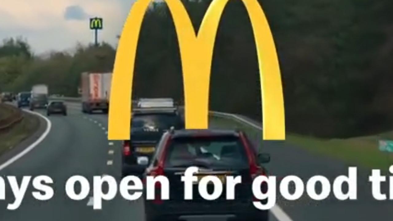Een still uit de video, waarop de grote M op de achtergrond is te zien boven de bossen.