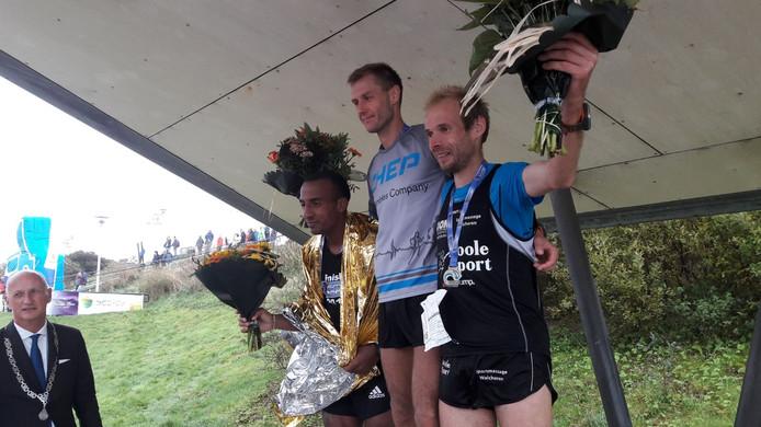 Het podium van de Kustmarathon, met rechts Erwin Harmes.