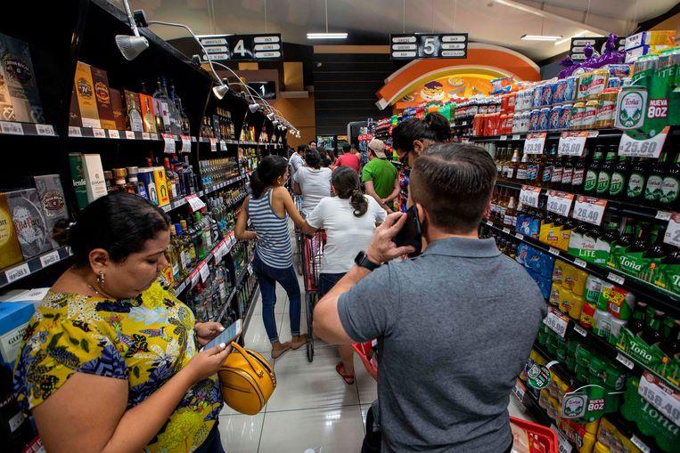Een supermarkt in de hoofdstad Managua, waar mensen in de rij wachten om af te rekenen. Beeld AFP