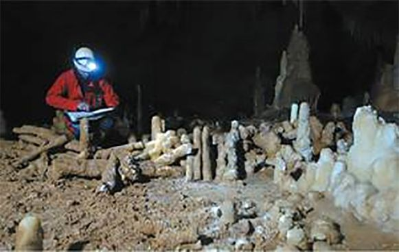 Archeoloog aan het werk bij een gestapelde structuur in de Neanderthalergrot van Bruniquel.