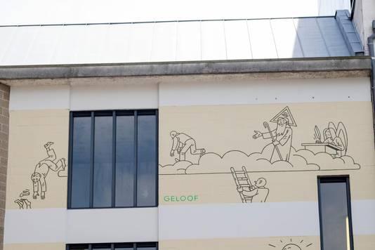 Een van de plaatjes op de stripmuur beeldt het geloof uit.