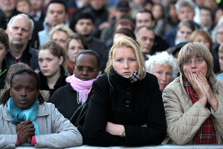 In Apeldoorn volgt het publiek de herdenkingsdienst voor de slachtoffers van de aanslag op Koninginnedag. (Joost van den Broek / de Volkskrant) Beeld Joost van den Broek